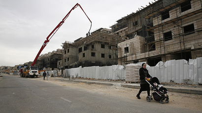 An ultra-Orthodox Jewish woman walks past a construction site in the West Bank Jewish settlement of Beitar Ilit, near Bethlehem, December 26, 2013. (Reuters / Baz Ratner)