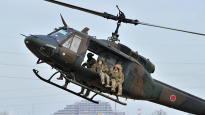 Camouflaged members of Japanese Ground Self Defense Forces' airbourne troop hold automatic rifles on a UH-1 helicopter during the new year exercise in Narashino in Chiba prefecture, suburban Tokyo on January 12, 2014 (AFP Photo / Yoshikazu Tsuno)