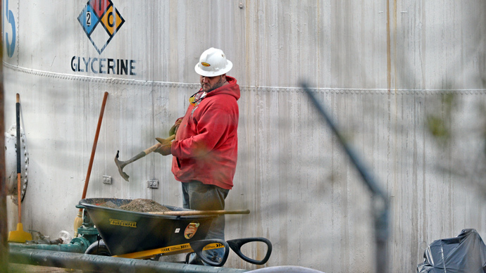 An unidentified worker at Freedom Industries shovels NAPA premium oil absorbent on January 10, 2014 in Charleston, West Virginia. (Tom Hindman / Getty Images / AFP)