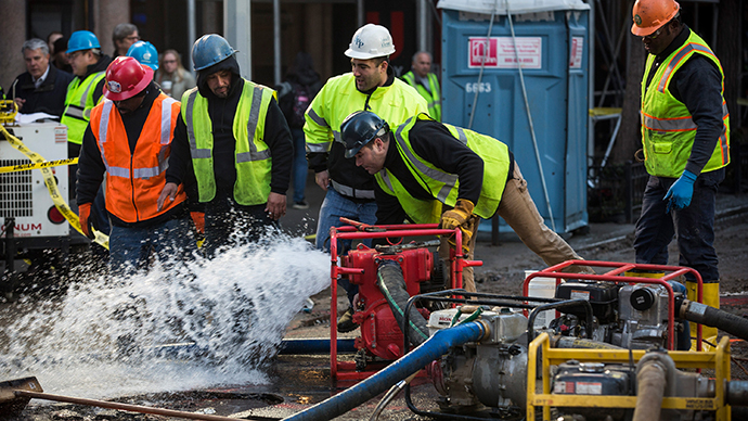 Workers use a generator to pump water out of a hole in the street, caused by a water main break on January 15, 2014 in New York City. (AFP Photo / Andrew Burton)