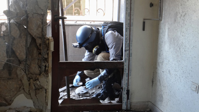 A United Nations (UN) arms expert collects samples on August 29, 2013, as they inspect the site where rockets had fallen in Damascus' eastern Ghouta suburb during an investigation into a suspected chemical weapons strike near the capital.  (AFP Photo / Ammar Al-Arbini)