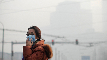 A woman wearing a face mask makes her way along a street  in Beijing on January 16,2014. (AFP Photo / Wang Zhao)