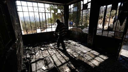 A Palestinian man walks inside his torched house in the West Bank village of Sinjil, near Ramallah November 14, 2013.(Reuters / Mohamad Torokman)