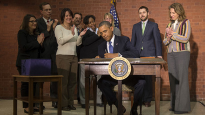 US President Barack Obama signs the 1.1 trillion-dollar omnibus spending bill at the New Executive Office Building, across the street from the White House, in Washington on January 17, 2014. (AFP Photo/Jim Watson)