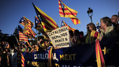 Demonstrators hold a giant banner and Catalan independentist flags during a protest as part of a campaign for independence from Spain, at the Pedralbes Palace in Barcelona during the first Economic Forum of the Western Mediterranean on October 23, 2013. (AFP Photo)