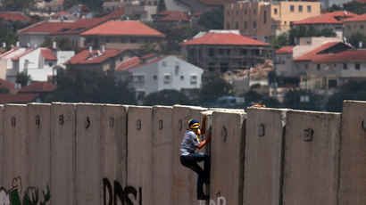 A Palestinian protester climbs Israel's controversial separation barrier during clashes with Israeli security forces following a demonstration against Israeli settlements and its separation wall, in the West Bank village of Nilin near the Jewish settlement of Hashmonaim (background), on June 14, 2013.(AFP Photo / Abbas Momani)