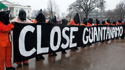 Protestors wear orange detainee jumpsuits and black hoods as they hold a banner calling for the closing of the US detention center at Guantanamo naval base in Cuba in front of the White House in Washington on January 11, 2014 to mark the 12th anniversary of the arrival of the first detainees at the controversial jail. (AFP Photo/Nicholas Kamm)