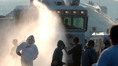 Protesters are hit with a water cannon by the PSNI (Police Service of Northern Ireland) (AFP Photo)