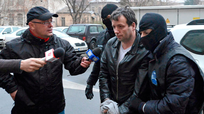 Marcel Lazar Lehel, 40, is escorted by masked policemen in Bucharest, after being arrested in Arad, 550 km (337 miles) west of Bucharest January 22, 2014.(Reuters / Silviu Matei)