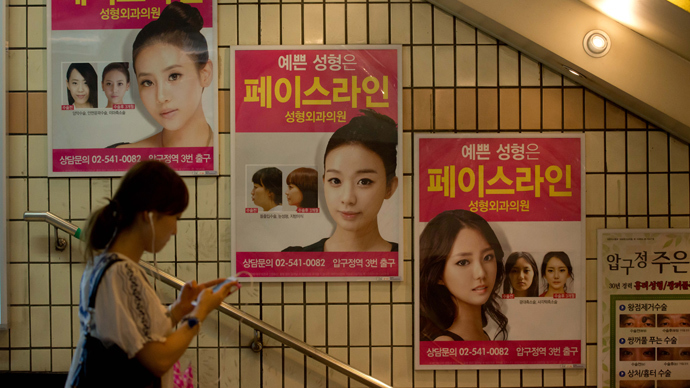 Advertisements for plastic surgery clinics are displyed at a subway station in Seoul. (AFP Photo / Ed Jones)