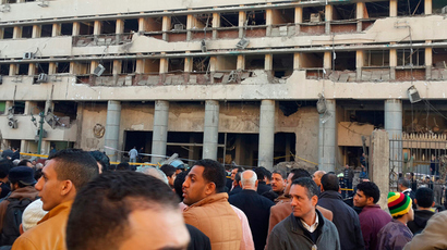 Police officers and people gather in front of the destroyed Islamic Museum building, after a bomb blast occurred at the police headquarters nearby, in downtown Cairo, January 24, 2014. (Reuters / Amr Abdallah Dalsh)