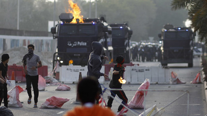 Anti-government protesters throw a Molotov cocktail and stone at riot-police armored personnel carriers during clashes after the funeral procession of Fadhel Abas Muslim in the village of Diraz, west of Manama, January 26, 2014. (Reuters/Hamad I Mohammed)