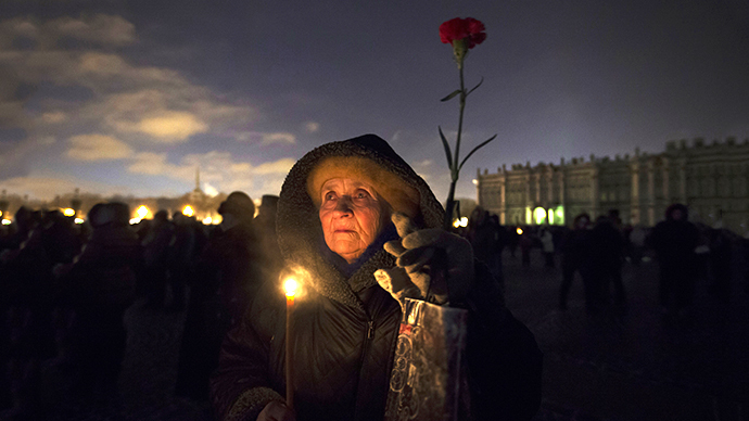 "A participant in ""The Candle of Memory"" action dedicated to the 70th anniversary of the full liberation of Leningrad from Nazi siege, in St.Petersburg's central Palace Square. (RIA Novosti / Igor Russak)"