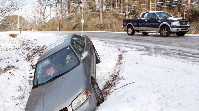 A driver uses a mobile phone in a car after running off the roadway due to a snow storm in Atlanta, Georgia, January 29, 2014. (Reuters / Tami Chappell)