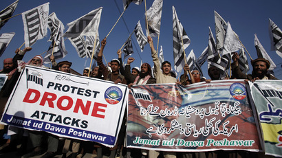 Supporters of the Jamaat-ud-Dawa Islamic organization hold placards and party flags as they shout slogans during a protest against U.S. drone attacks in the Pakistani tribal region, in Peshawar November 29, 2013. (Reuters/Fayaz Aziz)