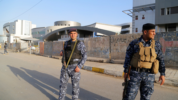 Iraqi policemen stand guard in front of the Ministry of Transportation building after an attack by suicide bombers in Baghdad January 30, 2014. (Reuters / Thaier al-Sudani)