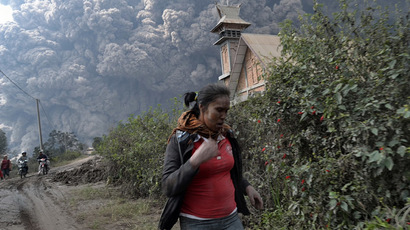 A woman flees as Mount Sinabung erupts near Bekerah village, in Karo district, North Sumatra, on February 1, 2014 (AFP Photo/Sutanta Aditya)