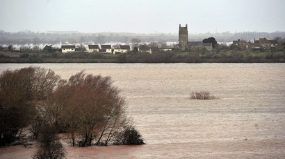 A village flanked by flooded fields is pictured near Curload in Somerset, southwest England, on February 1, 2014. (AFP Photo/Carl Court)