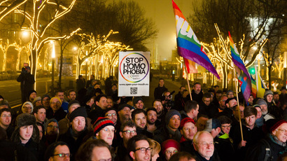 People hold a placard and rainbow flags as they call on the Russian authorities to lift anti-gay laws ahead of the Sochi 2014 Olympics during a protest outside the Russian embassy in Berlin, December 12, 2013. (Reuters/Thomas Peter)