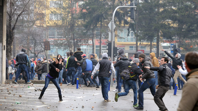 Protesters throw stones at police in front of a local government building in the northern Bosnian town of Tuzla, on February 6, 2014.(AFP Photo / Stringer)