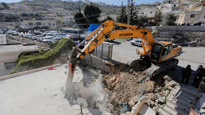 A bulldozer demolishes a house in Jabel Mukaber, a Palestinian village in the suburbs of East Jerusalem February 5, 2014.(Reuters / Ammar Awad)
