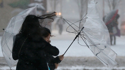 A woman holds onto a damaged umbrella due to strong winds during a heavy snowfall in Tokyo February 8, 2014 (Reuters / Toru Hanai)