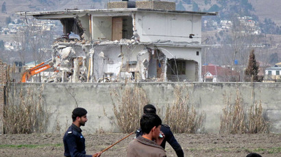 Policemen and residents stand near while demolition work is carried out on the building where al Qaeda leader Osama bin Laden was killed by U.S. special forces in Abbottabad.(Reuters / Sultan Dogar)