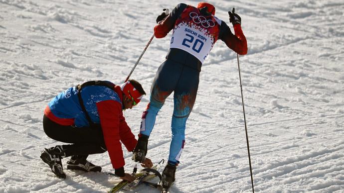 Canadian coach Justin Wadsworth fastens a ski to the foot of Russian athlete Anton Gafarov (RIA Novosti / Konstantin Chalabov)