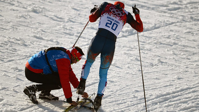 Canadian coach Justin Wadsworth fastens a ski to the foot of Russian athlete Anton Gafarov (RIA Novosti / Konstantin Chalabov)