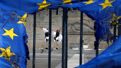 Presidential guards are framed through a burned EU flag in front of the Tomb of the Unknown Soldier by the parliament in central Syntagma square in Athens.(Reuters / Yannis Behrakis )