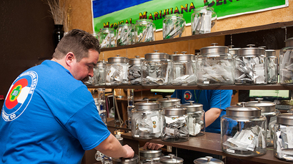 Sam Walsh, a budtender, sets up marijuana products as the 3-D Denver Discrete Dispensary prepares to open for retail sales on January 1, 2014 in Denver, Colorado. (AFP Photo / Theo Stroomer)