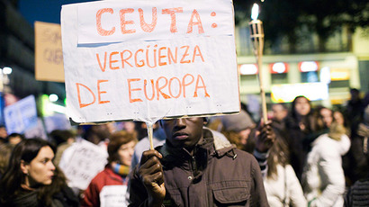 "An immigrant holds a placard during a protest for the death of at least nine immigrants in Spain's North African enclave of Ceuta a week ago while they were trying to enter Spain, in Madrid February 12, 2014. The placard reads ""Ceuta: shame of Europe"". Picture taken February 12, 2014. (Reuters / Juan Medina)"