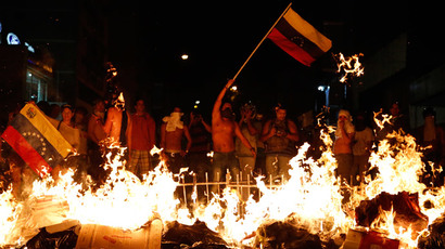 Opposition demonstrators hold a Venezuelan flag in front of a burning barricade during a protest against President Nicolas Maduro's government in Caracas February 15, 2014.(Reuters / Carlos Garcia Rawlins )