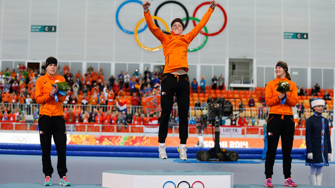 First-placed Jorien ter Mors (C) of the Netherlands jumps on the podium, as second-placed Ireen Wust (L) of the Netherlands and third-placed Lotte Van Beek (R) of the Netherlands look on, during the flower ceremony for the women's 1,500 metres speed skating event at the Adler Arena during the 2014 Sochi Winter Olympics, February 16, 2014 (Reuters / Issei Kato)