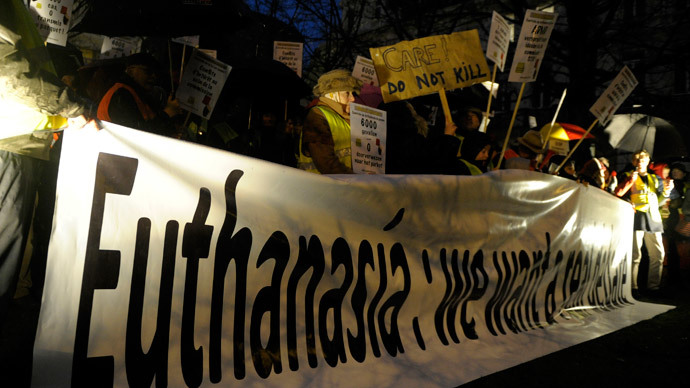 "Protesters, who call themselves the ""yellow jackets"", hold banners and placards as they demonstrate against a new law authorizing euthanasia for children, in Brussels February 11, 2014. (Reuters / Laurent Dubrule)"