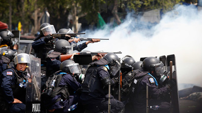 Thai policemen aim their weapons towards anti-government protesters during clashes near Government House in Bangkok February 18, 2014.(Reuters / Athit Perawongmetha )