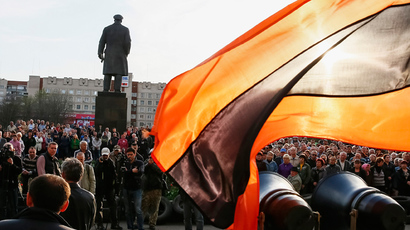A flag in the colours of the Ribbon of Saint George, which has become a symbol of anti-goverment sentiment, flutters as anti-goverment supporters gather outside the mayor's office in Slaviansk April 18, 2014 (Reuters / Gleb Garanich)