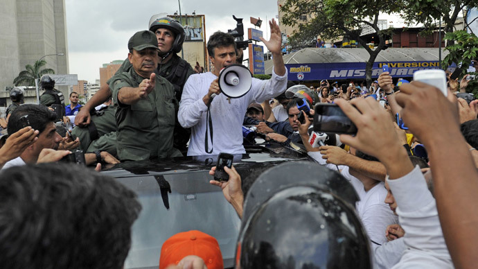 Leopoldo Lopez (C), an ardent opponent of Venezuela's socialist government facing an arrest warrant after President Nicolas Maduro ordered his arrest on charges of homicide and inciting violence, uses a megaphone to calm supporters down after they blocked the way to the national guard personnel who were transporting him after his surrender, during a demonstration in Caracas, on February 18, 2014. (AFP Photo / Leo Ramirez)