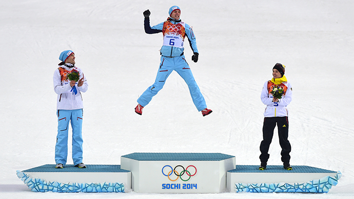 Norway's gold medalist Joergen Graabak (C) celebrates on the podium as Norway's Magnus Hovdal Moan (L) and Germany's Fabian Riessle (R) react during the Nordic Combined Individual LH / 10 km Flower Ceremony at the RusSki Gorki Jumping Center during the Sochi Winter Olympics on February 18, 2014. (AFP Photo / John Macdougall)