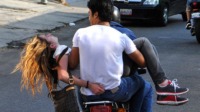 Opposition supporter Genesis Carmona is evacuated on a motorcycle after being shot in the head during a protest against Nicolas Maduro's government in Valencia, some 100 miles (160 km) from Caracas, February 18, 2014.(Reuters / Mauricio Centeno-Notitarde )