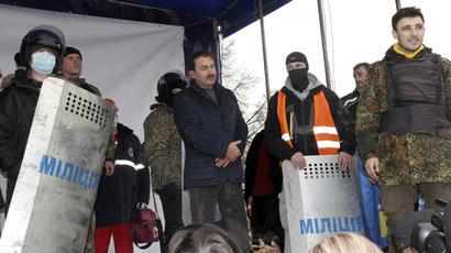 Volyn Region Governor Alexander Bashkalenko (2nd L, front) stands on the stage after he was captured by anti-government protesters during a rally in the town of Lutsk in northwestern Ukraine, February 19, 2014. (Reuters/Petro Krivoshey); Yotube video courtesy of serialu2014