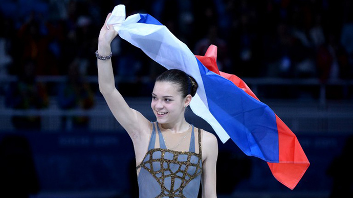 Russia's gold medalist Adelina Sotnikova waves a Russian flag during the Women's Figure Skating Flower Ceremony at the Iceberg Skating Palace during the Sochi Winter Olympics on February 20, 2014. (AFP Photo / Yuri Kadobnov)
