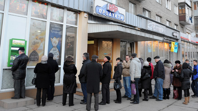 People queue to get their money from bank machine in the western Ukrainian city of Lviv on February 20, 2014, as a result of the financial panic caused with clashes between anti-government opposition and police in Kiev. (AFP Photo)