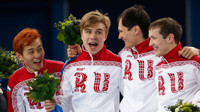 The winning Russian team celebrates on the podium during the flower ceremony for the men's 5,000 metres short track speed skating final relay race at the Iceberg Skating Palace in the Sochi 2014 Winter Olympic Games February 21, 2014.(Reuters / David Gray)