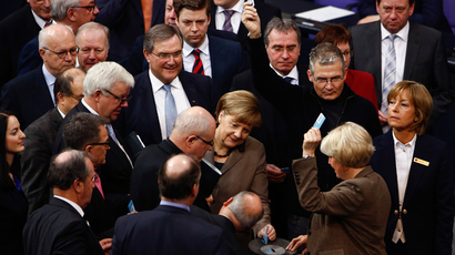 German Chancellor Angela Merkel (C) lines up with fellow parliamentarians to cast their votes after a debate about deputy allowances and graft at the lower house of parliament, the Bundestag, in Berlin (Reuters / Thomas Peter)
