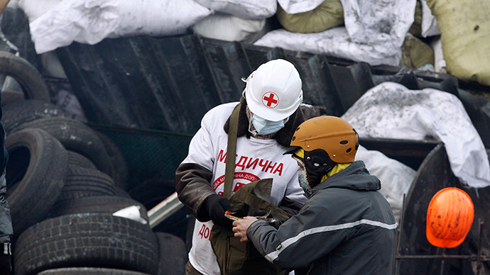 A medical volunteer helps an anti-government protester at the site of clashes with riot police in Kiev (Reuters / Vasily Fedosenko)