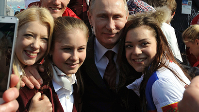 Russian President Vladimir Putin (C) and Russian Olympic medal winning athletes pose for a picture in Sochi February 24, 2014 (Reuters / Mikhail Klimentyev)