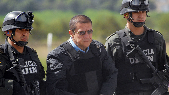 "This December 12, 2008 file photo shows Diego Montoya (C), aka ""Don Diego"", the then alleged head of Colombia's Norte del Valle drug cartel and one of the most wanted drug traffickers by the US justice, being led under heavy police escort in Bogota to be extradited to the US. (AFP Photo/Luis Ramirez)"