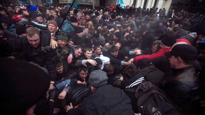 Ukrainian men help pull one another out of a stampede during clashes at rallies held by ethnic Russians and Crimean Tatars near the Crimean parliament building in Simferopol February 26, 2014.(Reuters / Baz Ratner)