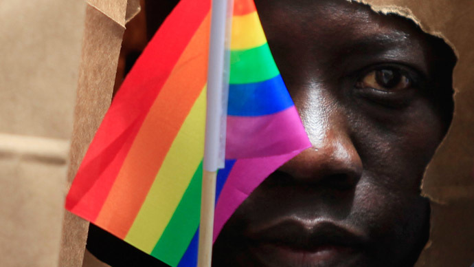 An asylum seeker from Uganda covers his face with a paper bag in order to protect his identity as he marches with the LGBT Asylum Support Task Force during the Gay Pride Parade in Boston, Massachusetts June 8, 2013. (Reuters/Jessica Rinaldi)
